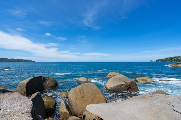 Rocky seashore under clear blue sky with clouds in the morning summer sunny day background beautiful sea in phuket thailand.