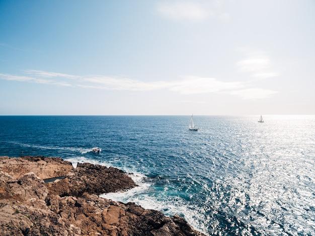 岩の多い海岸の帆船は、明るい太陽の下で遠くを航行します