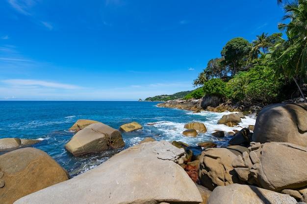 아침에 구름과 나뭇잎 나무 프레임 배경 맑고 푸른 하늘 아래 바위 해변 아름 다운 바다와 태국 푸 켓에서 작은 섬.