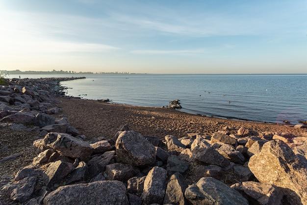 ロシア、サンクトペテルブルクの朝日の下の岩の多い海岸。