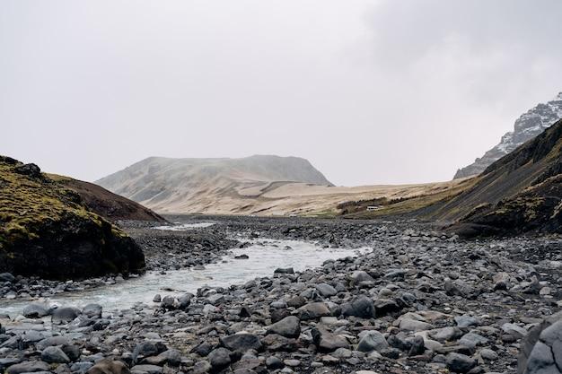 アイスランドの岩だらけの浅い山川は、山々を背景に流れています。