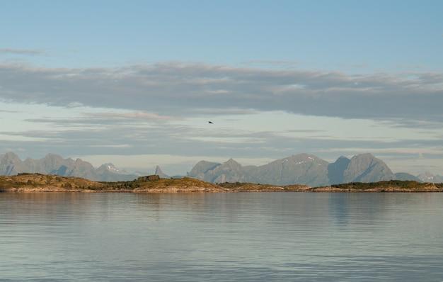 저녁에 수평선에 물 위의 바위 해안, lofoten, 노르웨이