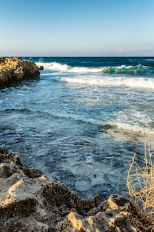 The rocky shore of the beautiful blue sea on a sunny day