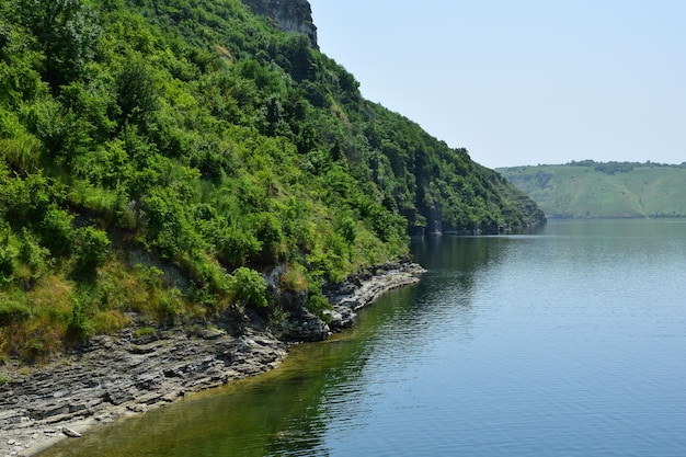 Rocky shore of the lake overgrown with trees and bushes at the foot of the mountain