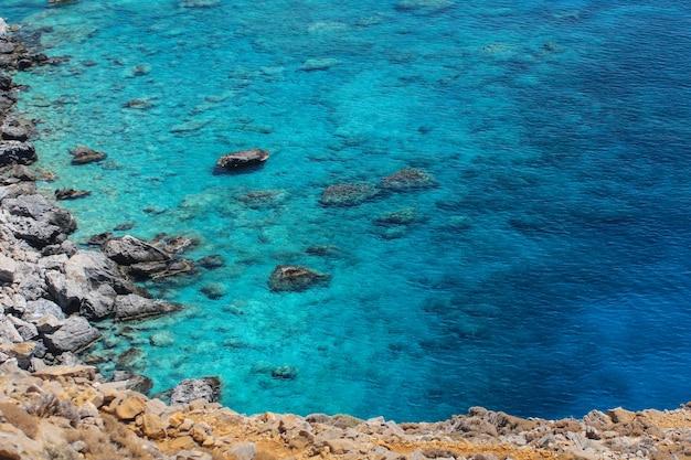 晴れた日に水の近くの岩の多い海岸