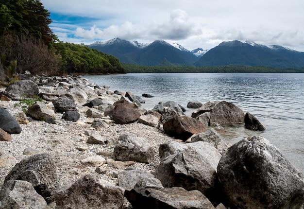 湖の岩の多い海岸と山々を背景に湖マナポウリフィヨルドランドニュージーランド