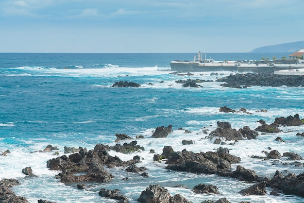Rocky shore of puerto de la cruz. waves of atlantic ocean roll over the rocks on a sunny day, tenerife, spain