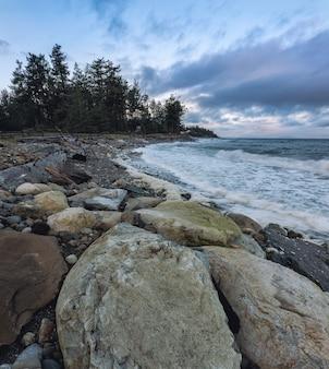 흐린 하늘 아래 바위 해안 무료 사진