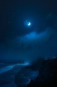 満月の下の岩の多い海岸