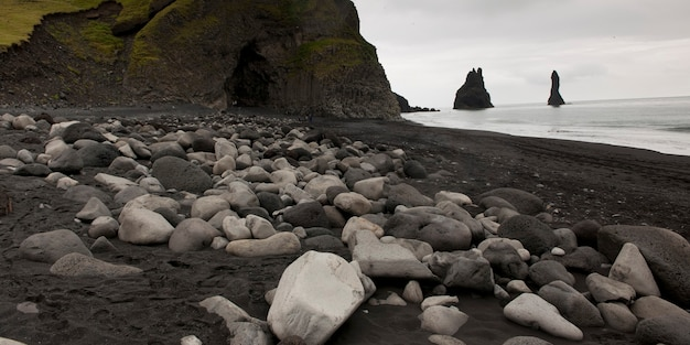 Rocky shoreline with cave, black volcanic sand, stacks offshore