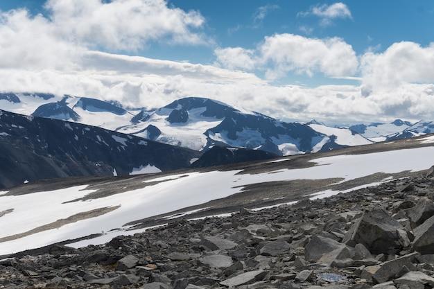 Jotunheimen 국립 공원, 노르웨이의 눈 덮인 산의 배경에 대해 바위 경사면