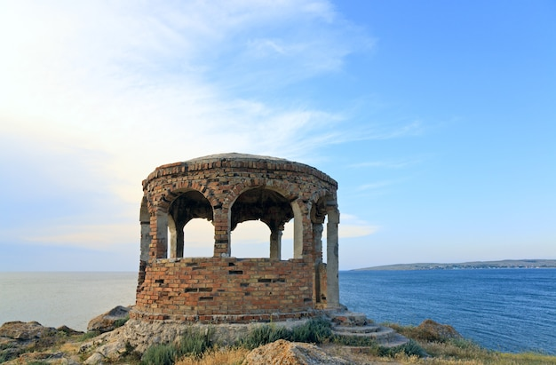 Rocky summer coastline and cape with pavilion on blue sky background