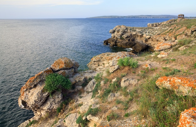 Rocky summer coastline and cape with pavilion