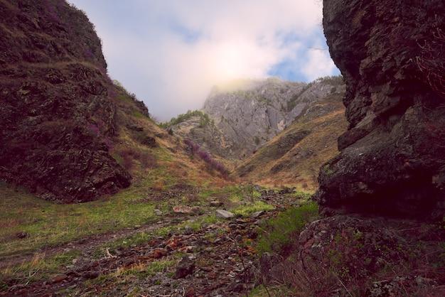 Каменистая тропа по дну ущелья с крутыми живописными склонами