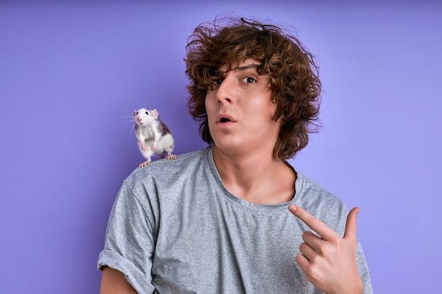 설치류 훈련 및 길들이기. 어깨에 장식용 쥐를 가진 수컷, 젊은 수컷은 재미있는 얼굴을 만들고 찡그린 다. 격리 된 보라색 배경
