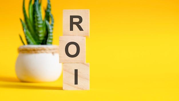 テーブル、黄色の背景に木製のブロックとロイの概念