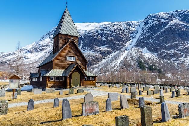 雪キャップ山背景を持つroldal stave教会(roldal stavkyrkje)