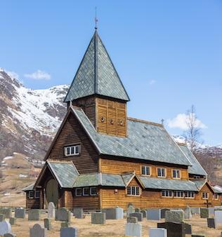 Деревянная церковь ролдал (roldal stavkyrkje) на фоне снежной шапки горы