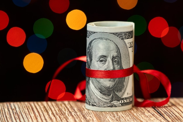 Roll of 100 us dollar bills with ribbon against of colorful lights