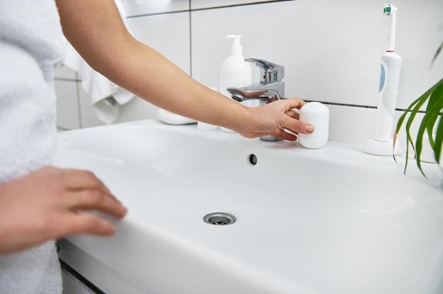 A roll-on antiperspirant on the bathroom washsbasin.