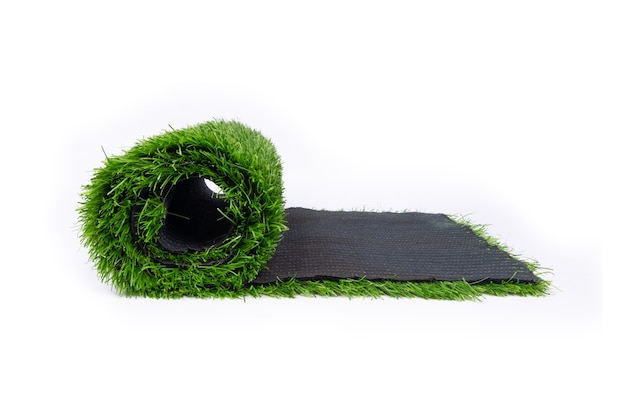 Roll of artificial turf isolated on white wall, coating for sports grounds.