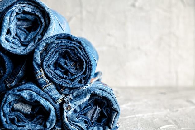 灰色の背景に青いデニムジーンズをロールします。