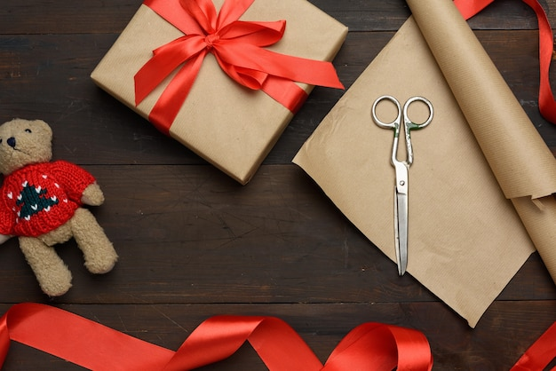 Roll of brown kraft packaging paper, box tied with a red silk ribbon, scissors and a bobbin with ribbon on a brown wooden background, top view
