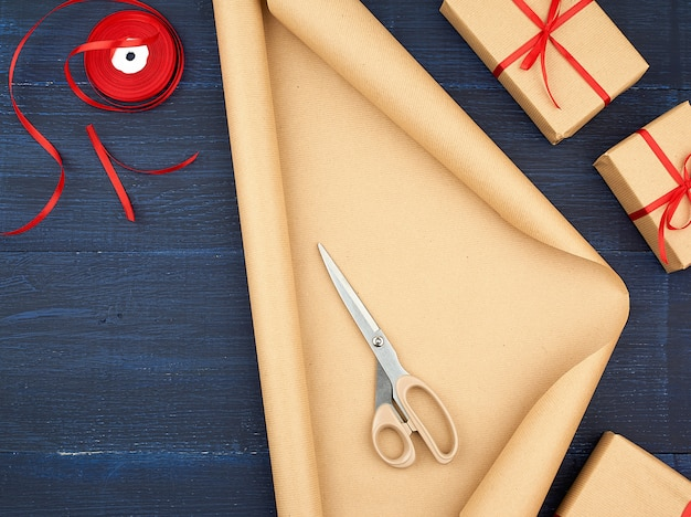 Roll of brown kraft packaging paper, box tied with a red silk ribbon, scissors and a bobbin with ribbon