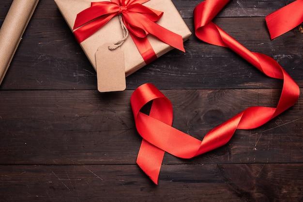 Roll of brown kraft packaging paper, red silk ribbon on brown wooden, top view