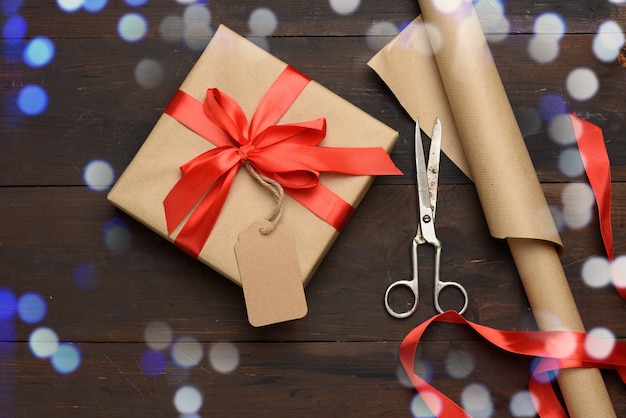 Roll of brown kraft packaging paper, red silk ribbon, scissors and a bobbin with ribbon on brown wooden, top view