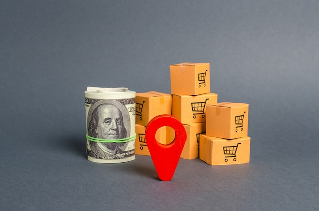 Roll bundle of dollars, red pointer location and cardboard boxes.