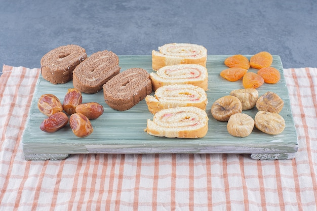 大理石の背景に、ボード上でケーキとドライフルーツをロールバックします。