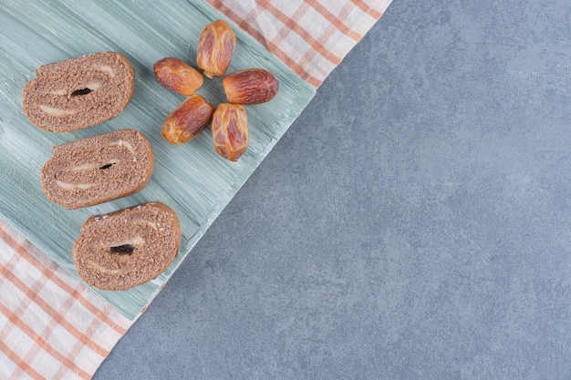 Roll cake and dried fruits on the board , on the marble background.