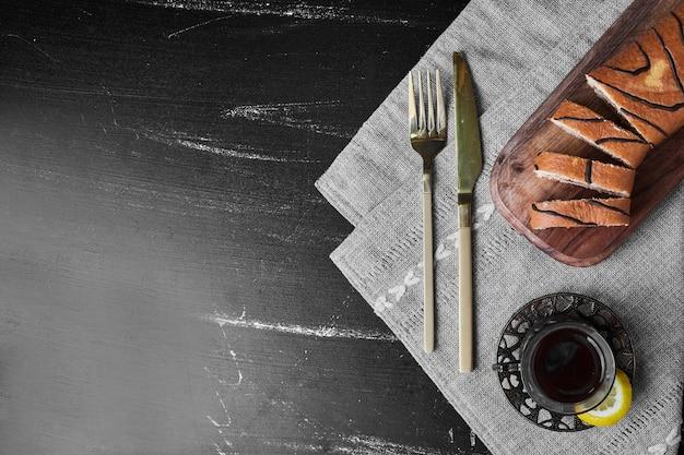 お茶のグラス、上面図と木の板の上にケーキのスライスを転がします。