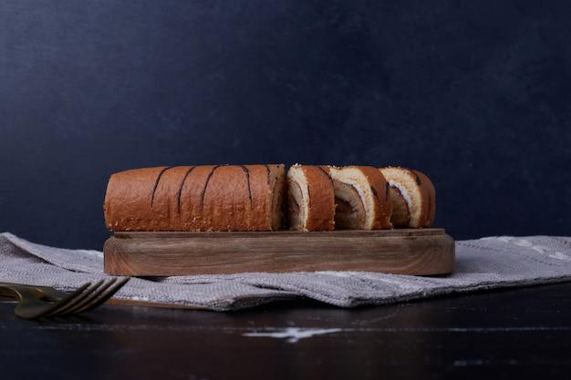 Раскатайте кусочки торта на деревянной доске.