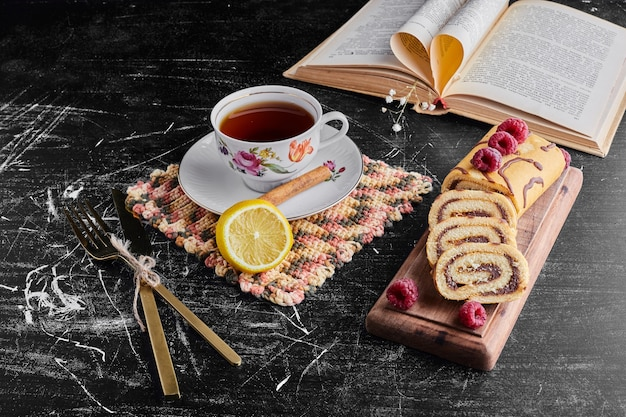 Rotolo di torta con cioccolato e frutti di bosco e una tazza di tè.