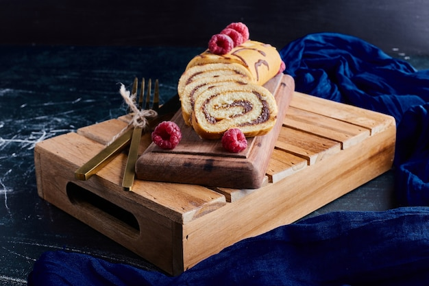 Roll cake with chocolate and berries on a wooden tray.