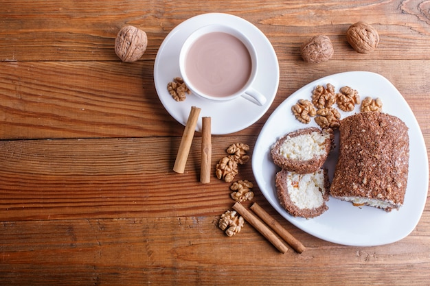 Roll cake with curd and walnuts isolated on brown wooden background.