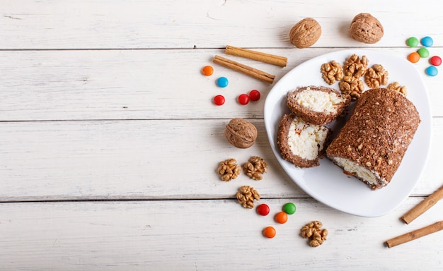 Roll cake with curd and walnuts isolated on white wooden background.