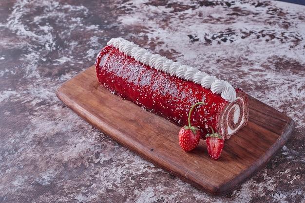 周りに果実のある木の板に赤いマーマレードが付いたケーキをロールバックします。