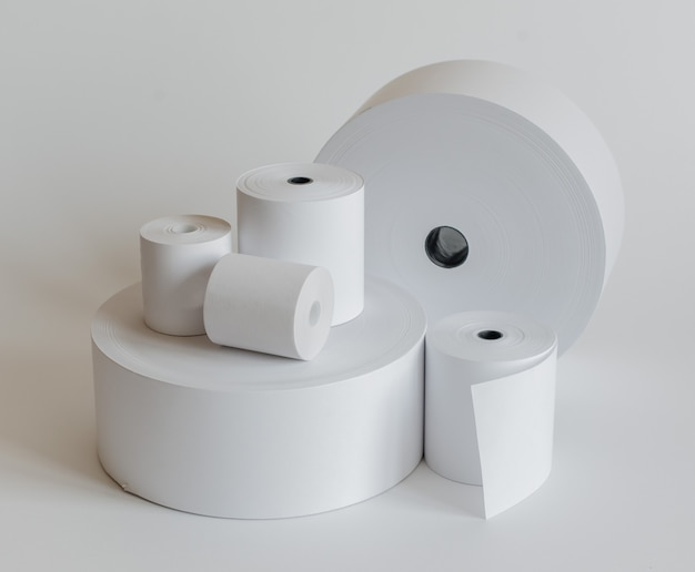 Roll of cash register tape isolated on soft gray .