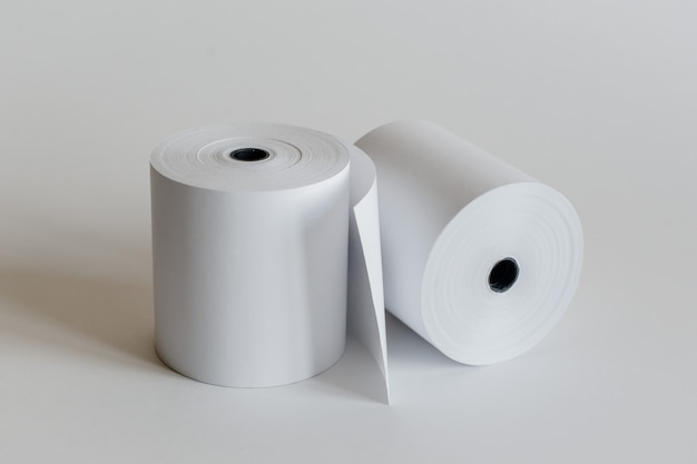 Roll of cash register tape isolated on soft gray.