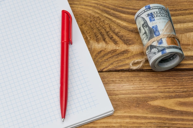 A roll of dollars, a notebook and a pen lie on a wooden textured table.