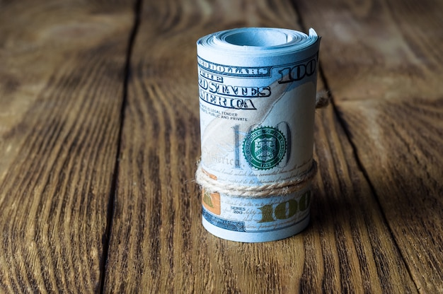 A roll of dollars stands on a wooden textured table.