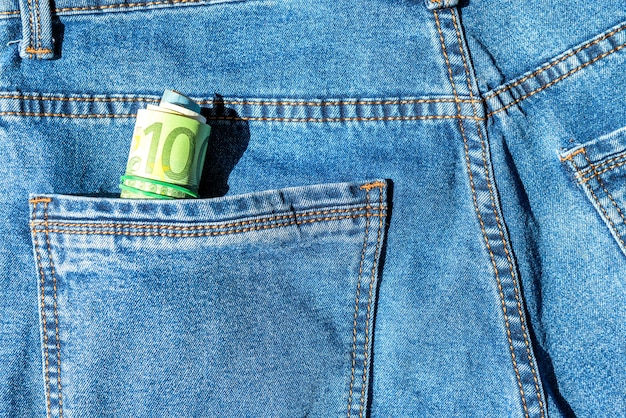 Roll of euro banknotes in a blue jeans pocket