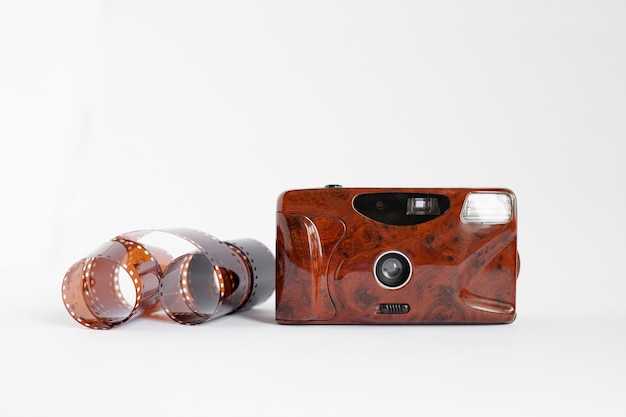 A roll film and a film retro camera of red color on a white isolated surface. analog photography concept