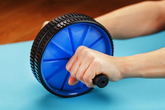 Рулон для тренировки пресса в руках на синем коврике.