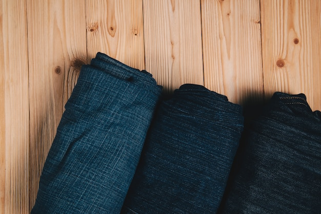 Roll frayed jeans or blue jeans denim collection on wood