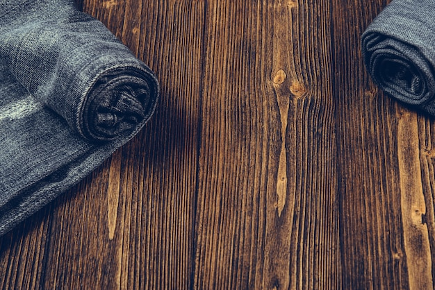 Roll frayed jeans or blue jeans denim on dark wood