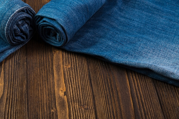 Roll frayed jeans or blue jeans denim on rough dark wood